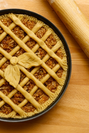 Apple pie in baking tray, wooden rolling pin with white wheat flour on the table Stock Photo - 22839732