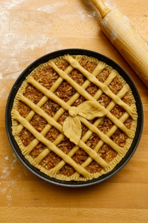 Apple pie in baking tray, wooden rolling pin with white wheat flour on the table photo