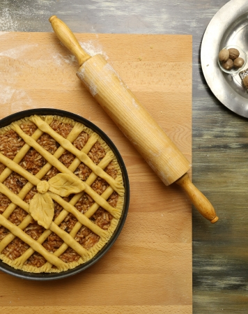 white backing: Apple pie in baking tray, wooden rolling pin with white wheat flour on the table