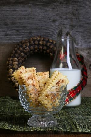 breadsticks: Palitos de pan de az�car de canela caseros grisines con una botella de leche y pi�a corona de flores con la cinta de Navidad en el fondo