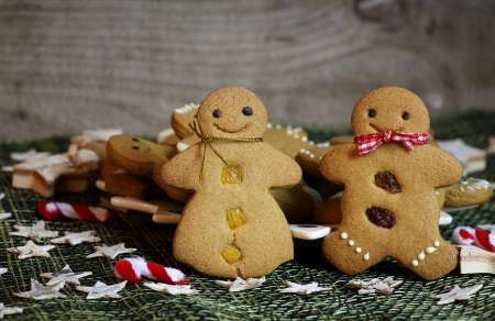 Happy Gingerbread couple with christmas decoration and gingerbread cookies in background, birch stars photo