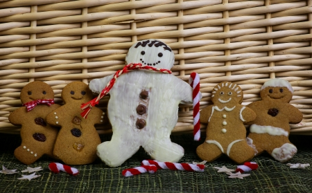 Gingerbread family snowman with gingham ribbons, green ribbon and christmas decoration, wicker basket in background photo