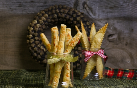 Homemade Parmesan Cheese breadsticks Grissini with salted grissini in jar and pinecone wreath with christmas ribbon in background