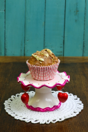 Banana Walnut muffin with white chocolate and cinnamon on colorful ceramic stand and rustic turquoise background photo