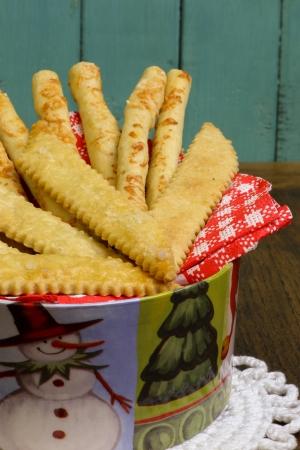 breadsticks: Palitos de pan hecho en casa del queso parmesano Grissini con grisines salados en lata caja de navidad y fondo azul turquesa Foto de archivo