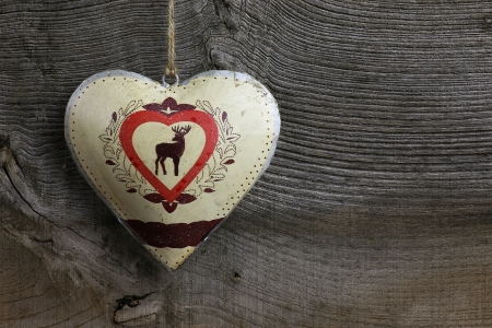 deer in heart: Christmas handmade decoration deer in tin heart over rustic Elm wood background - retro style design, copy space