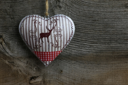 Christmas handmade decoration deer in tin heart over rustic Elm wood background - retro style design, copy space photo