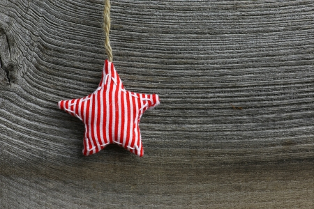 Christmas handmade decoration red stripes fabric star over rustic Elm wood background - retro style design, copy space photo