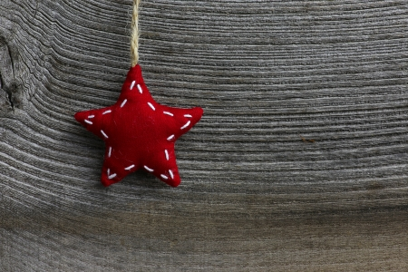Christmas handmade decoration red fabric star over rustic Elm wood background - retro style design, copy space Stock Photo
