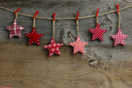 old fashioned christmas: Christmas handmade decoration red and white pattern fabric stars over rustic Elm wood background - retro style design, copy space