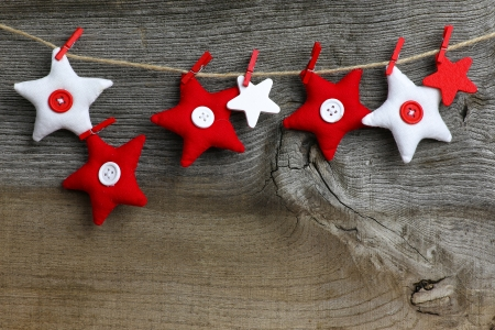 Christmas handmade decoration red and white fabric stars over rustic Elm wood background - retro style design, copy space photo