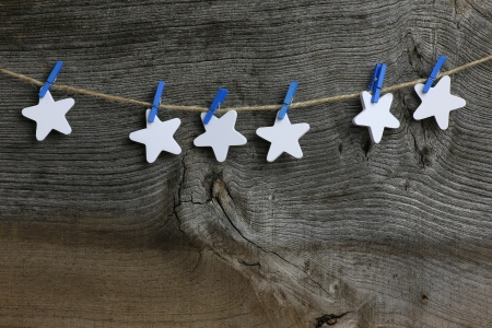 Christmas handmade decoration white wooden stars and blue clips over rustic Elm wood background - retro style design, copy space photo