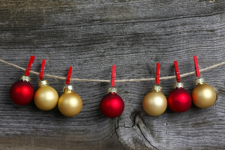 Christmas hanging decoration red and gold bulbs with red clips over rustic Elm wood background - retro style design, copy space photo