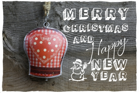 Merry Christmas message, handmade decoration gingham heart pattern on tin bell over rustic Elm wood background - retro style design photo