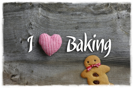I love baking message Christmas handmade decoration red stripes fabric hearth over rustic Elm wood background - retro style design, Gingerbread cookie Stock Photo