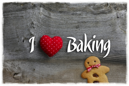 I love baking message Christmas handmade decoration polka dot fabric hearth over rustic Elm wood background - retro style design Gingerbread cookie