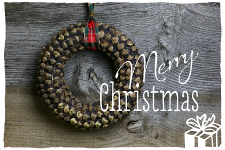 Merry Christmas message, handmade pinecone wreath decoration over rustic Elm wood background - retro style design photo