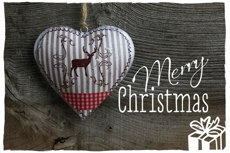Merry Christmas message, handmade decoration deer in tin heart over rustic Elm wood background - retro style design