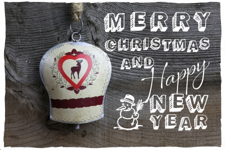 Merry Christmas message, handmade decoration deer on tin bell over rustic Elm wood background - retro style design photo