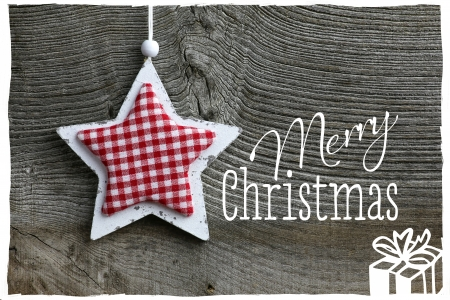 Merry Christmas message, handmade decoration Shabby Chic wooden star with gingham fabric pattern over rustic Elm wood background - retro style design