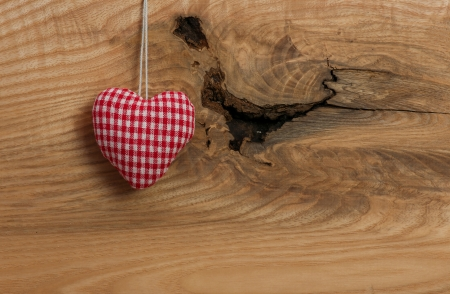 Love heart hanging on wooden texture background photo