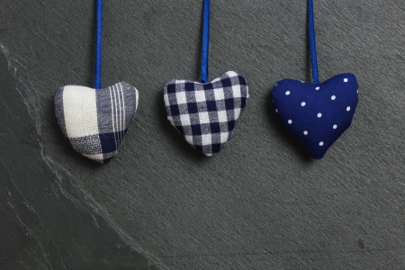 White Blue pattern Love Valentine s hearts hanging on grey slate stone background photo
