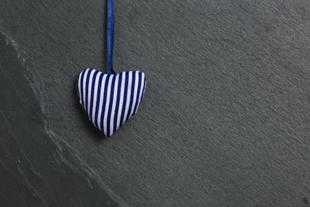 Wei�-blaue Streifen Liebe Valentine s Herz h�ngt an grauer Schiefer Hintergrund