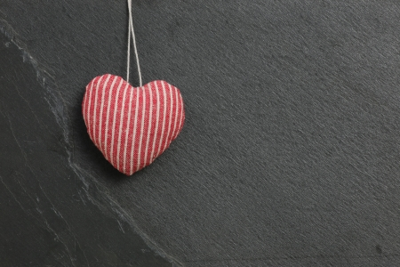 Red with White stripes Love Valentine s heart hanging on grey slate stone background photo
