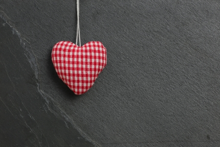 Red Gingham Love Valentine s heart hanging on grey slate stone background photo