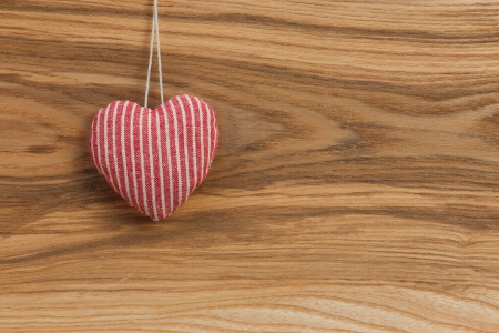 Love Valentine s heart hanging on wooden texture background photo