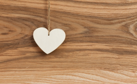 White Love Valentine s heart hanging on wooden texture background photo