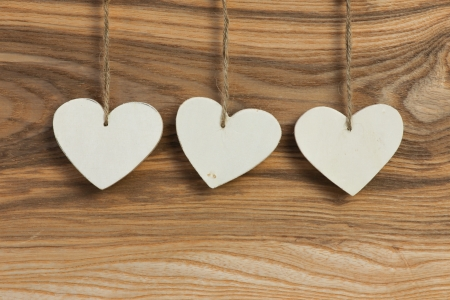 Three White Love Valentine s heart hanging on wooden texture background photo