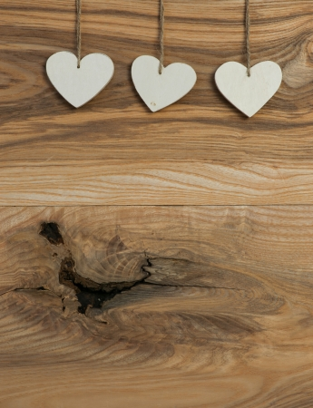 Three White Love Valentine s heart hanging on wooden texture background