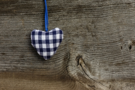 Blue gingham Love Valentine s heart hanging on wooden texture background photo