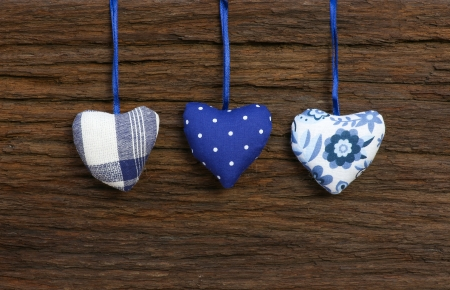 Blue pattern Gingham Love Valentine s hearts hanging on wooden texture background photo