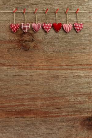 Gingham Love Valentine s hearts hanging on wooden texture background photo
