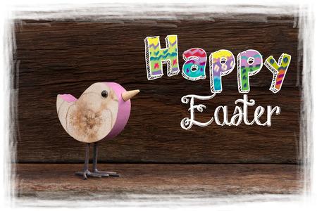 Happy easter text with pink wooden birch bird on dark rough background white frame