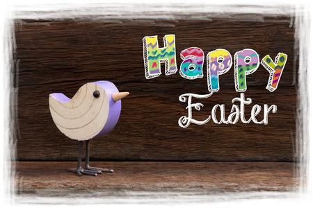 Happy easter text with purple wooden birch bird on dark rough background white frame