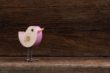Wooden pink toy bird figure symbol on old rough background with copy space Stock Photo