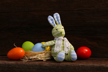 Easter Bunny Toy with colorful eggs in natural raffia nest on rough dark wooden background, copy space
