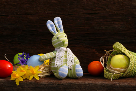 Easter Bunny Toy with small basket, colorful eggs, daffodils on rough dark wooden background, copy space