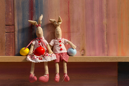 Happy easter bunny couple with eggs on painted background and copy space
