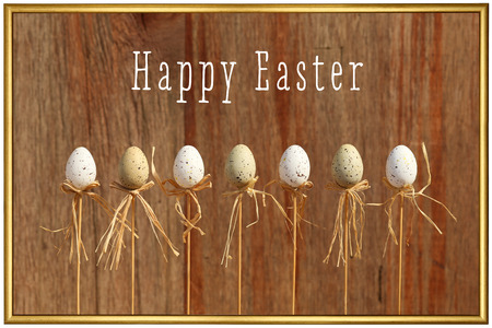 Happy easter text with marbled eggs on sticks and painted background golden frame Stock Photo