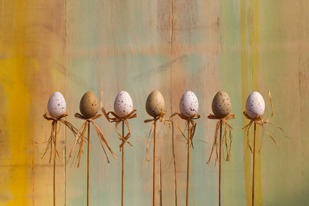 Happy easter text with marbled eggs on sticks and green painted background copy space