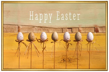 Happy easter text with marbled eggs on sticks and painted background golden frame photo