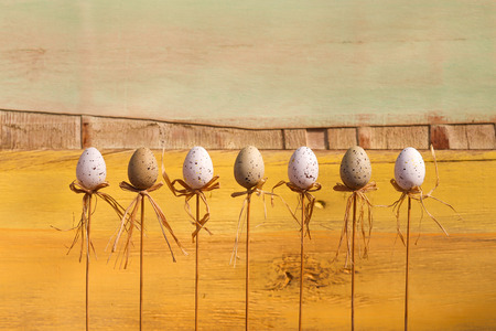 Happy easter text with marbled eggs on sticks and yellow green painted background copy space photo