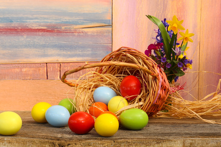 Happy easter text with painted eggs flowers wicker basket old  background copy space