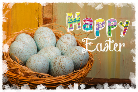 Happy easter text with painted duck eggs wicker basket old  background white frame Stock Photo