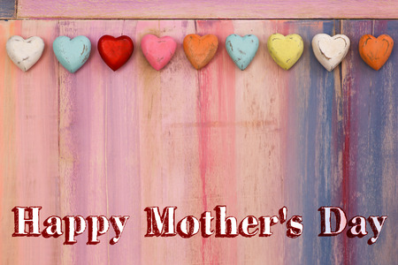 Happy mothers day message colorful painted board with wooden hearts photo