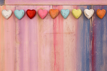 Love message space on colorful painted board with wooden hearts, copy space Stock Photo